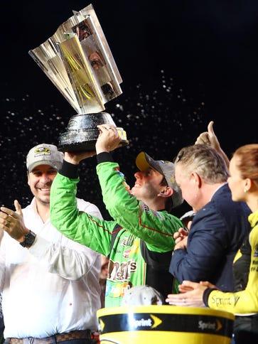 Kyle Busch hoists the Sprint Cup championship trophy