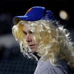 A fan wears a wig before Game 4 of the Major League Baseball World Series between the New York Mets and Kansas City Royals Saturday, Oct. 31, 2015, in New York.
