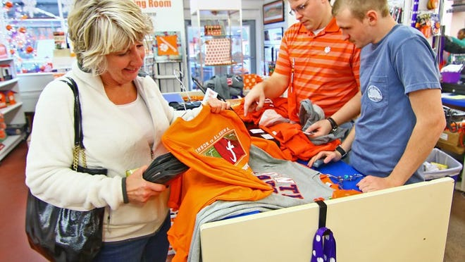 Photos by Ken Ruinard/Independent Mail Karen Craddock of Clemson looks at one of the many T-shirts she bought from Brett Schoonover (middle) and Elijah Collins at Mr. Knickerbocker in downtown Clemson. Craddock said she went to the 1981 championship game and didn't want to pass on the one in Arizona. Go to independentmail.com to see more photos.