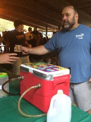 Eric Pedley, co-owner of the North Brewery in Endicott, serves a stout on Saturday during the annual Zoo Brew at the Binghamton Zoo at Ross Park. The event featured 10 area craft breweries.