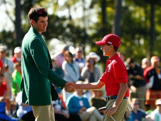 Bubba Watson (left) shakes hands with Naples' Sam Kodak (right) after his putt in the Boys 12-13 age group during the Drive, Chip and Putt National Finals at Augusta National GC in Augusta, Ga., on Sunday, April 2, 2017.