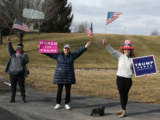 Supporters of U.S. President Donald Trump hold up signs as the presidential motorcade passes Sycamore High School on its way to Sheffer Corporation, Monday, Feb. 5, 2018, in Blue Ash.