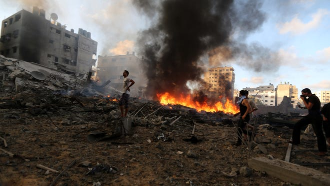 Palestinian rescuers inspect an area damaged in an Israeli airstrike in Gaza City, Thursday, July 24, 2014.