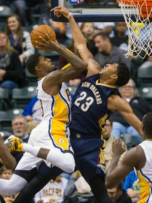 New Orleans Pelicans' Anthony Davis (23) tries unsuccessfully to block the shot of Indiana Pacers' Paul George (13) during the first half of their preseason  game.