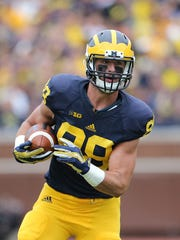 Jake Butt of the Michigan Wolverines runs for a short gain during the first quarter of the game against the Oregon State Beavers on September 12, 2015 at Michigan Stadium.