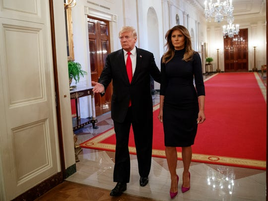 President Donald Trump and first lady Melania Trump arrive in the East Room of the White House where he signed sweeping legislation addressing the opioid crisis, one of her signature FLOTUS issues. Both also used the event to condemn the mailing of pipe bombs to former President Obama, former Secretary of State Hillary Clinton, CNN and other organizations on the same day. She wore a form-fitting navy sweater dress with a mock turtleneck collar for the occasion.