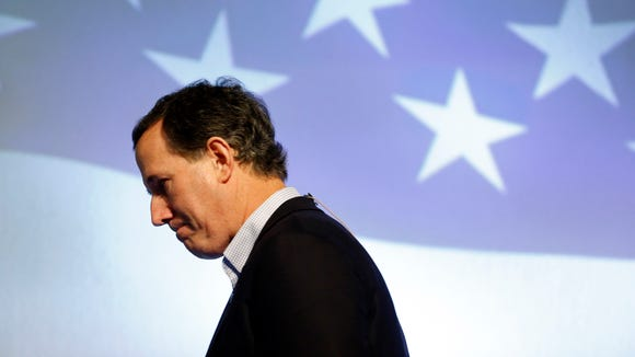 Rick Santorum walks off stage after speaking at the