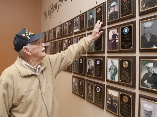 Gordon Lampitt touches his plaque one of 69 new plaques added to the New War Veterans Hall of Fame in Voorhees.