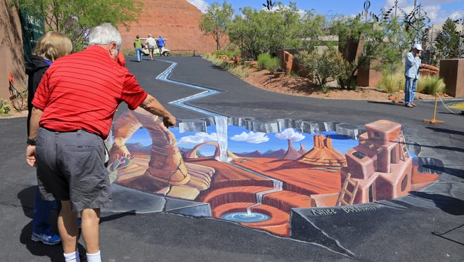 Visitors to the 2015 Kayenta Street Painting Festival admire a three-dimensional painting by local artist Aimee Bonham at Coyote Gulch Art Village in Ivins City. The semi-permanent paintings is still on display for this year's event.