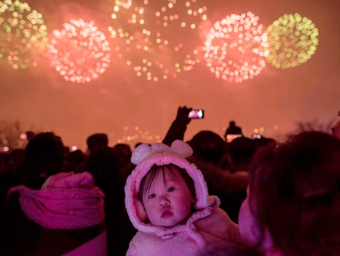 People watch a fireworks display as they visit an ice