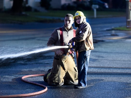 """Eight-year-old Landyn Kelchner and fire fighter Hunter McMullen practice putting out a """"fire"""" at the Neversink Fire Comapny's Open House."""