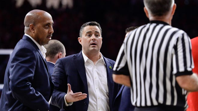 Arizona associate head coach Lorenzo Romar (left) and head coach Sean Miller argue a call with official Dick Cartmell on Jan 27, 2018, during a game against Utah at McKale Center.