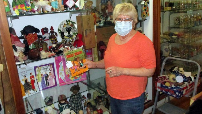 Karen Jacobs arranges some of her wares June 3 at the Victorian Rose Vintage shop on Route 20 in Bouckville. The antiques and collectibles stores on and along that strip from Madison to Bouckville are reopening for business.