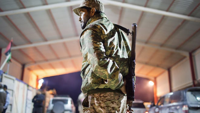 A Libyan military soldier stands guard at the entrance of a town 68 miles from Sirte, Libya, on Feb. 18, 2015.