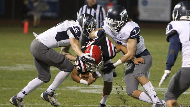 Brophy running back Ryan Velez is tackled by a pair of Pinnacle defenders in a playoff game at Phoenix College in Phoenix, Arizona on November 6, 2015.