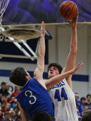 CovCath's Jake Walter puts in a sky hook over LexCath's TC Price during their game at CovCath, Wednesday, November 30, 2016.