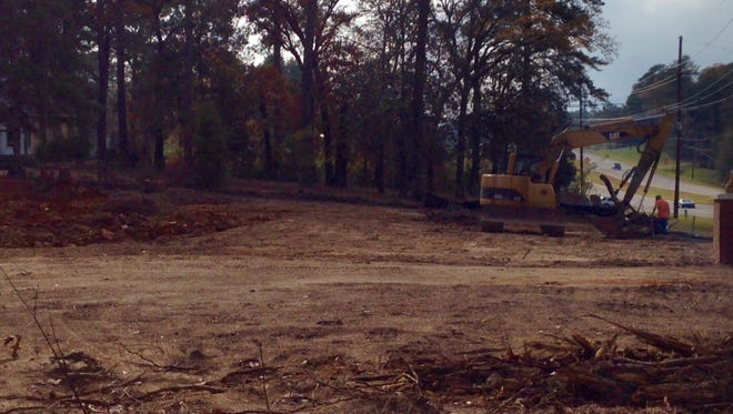 Workers clear land at the location of a planned Holiday Inn Express in Pineville.