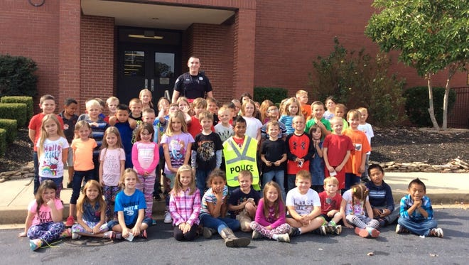 "West Pelzer Elementary School first graders would like to give a ""big shout out"" to Officer Andrew League, at center back, for reading to them."