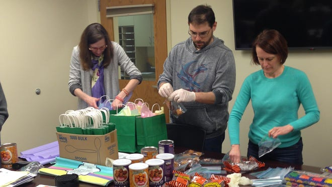 JFS board members Christine Harrop-Stein, left, Louis Mendlowitz, center, and Susan Marshall, right, prepare gift bags for distribution.