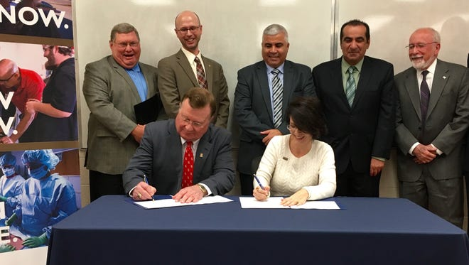 Joseph Savoie (seated, left), president of the University of Louisiana at Lafayette, and Natalie Harder (right), chancellor of South Louisiana Community College, on Tuesday sign an agreement that allows students to finish an associate's and a bachelor's degree in four years.