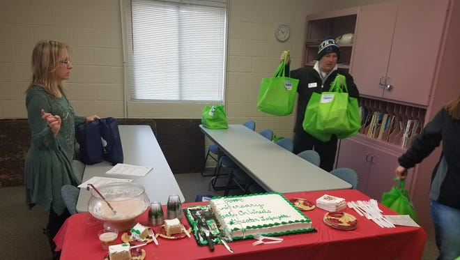 From left, Kristi Craft of Meals on Wheels of Greater Lafayette and Ryan Vanscoyoc of Bob Rohrman Subaru participate in the Subaru Share the Love event on Dec. 21, 2016.