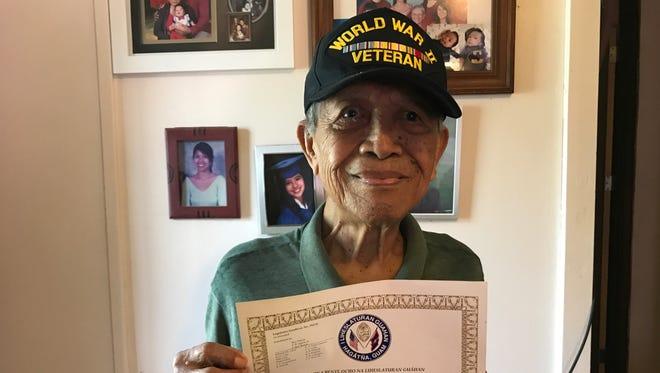 Lorenzo Batangan, a Filipino World War II veteran, shows a certificate from the Guam Legislature honoring his service.