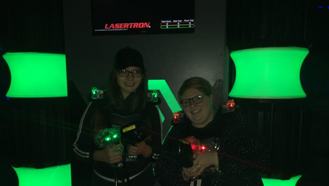 Job shadow Alexus Thibodeaux, left, and staff writer Megan Wyatt prepare for a game of laser tag at the newly opened arena at Acadiana Lanes in Lafayette, La.