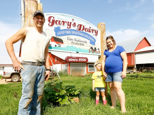 Gary Stankowski, left, his daughter Ella, and wife Holly, all of Mosinee, pose for a photo Wednesday at their dairy farm, Gary's Dairy.