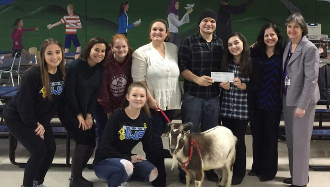 Jena and Anthony Mazzio accepted a $1,300 donation for the Ahimsa Acres Sanctuary from Washington Township High School principal Ann Moore, PAWS Club Advisor Karen LaRosa and members of the PAWS Club Executive Board.