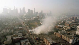 In this April 30, 1992 file photo, smoke rises from a shopping center burned by rioters in Los Angeles.