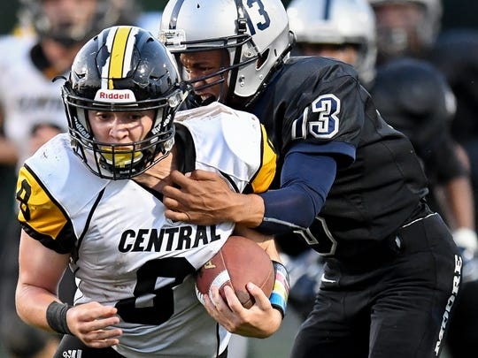 Johnson Central's Blake Gamble (8) is tackled by Moore High School's Josiah Tylor during the game played at Moore Traditional School, Friday, September 15, 2017.