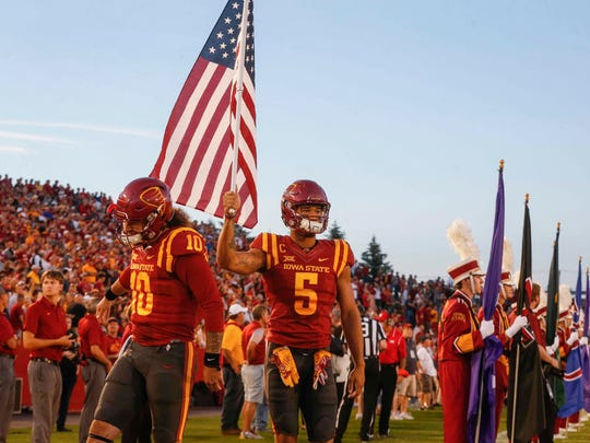 Iowa State senior receiver Allen Lazard carries the United States flag as the Cyclones take the field prior to kickoff against Texas on Thursday, Sept. 28, 2017, at Jack Trice Stadium in Ames.
