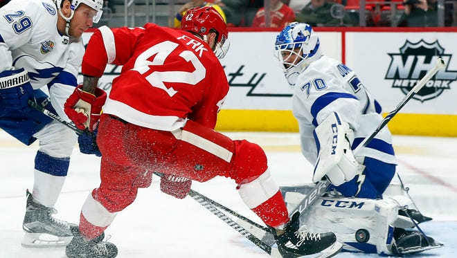 Lightning goaltender Louis Domingue (70) stops a shot by Red Wings right wing Martin Frk (42) as Lightning's Slater Koekkoek (29) defends in the second period on Sunday, Jan. 7, 2018, at Little Caesars Arena.