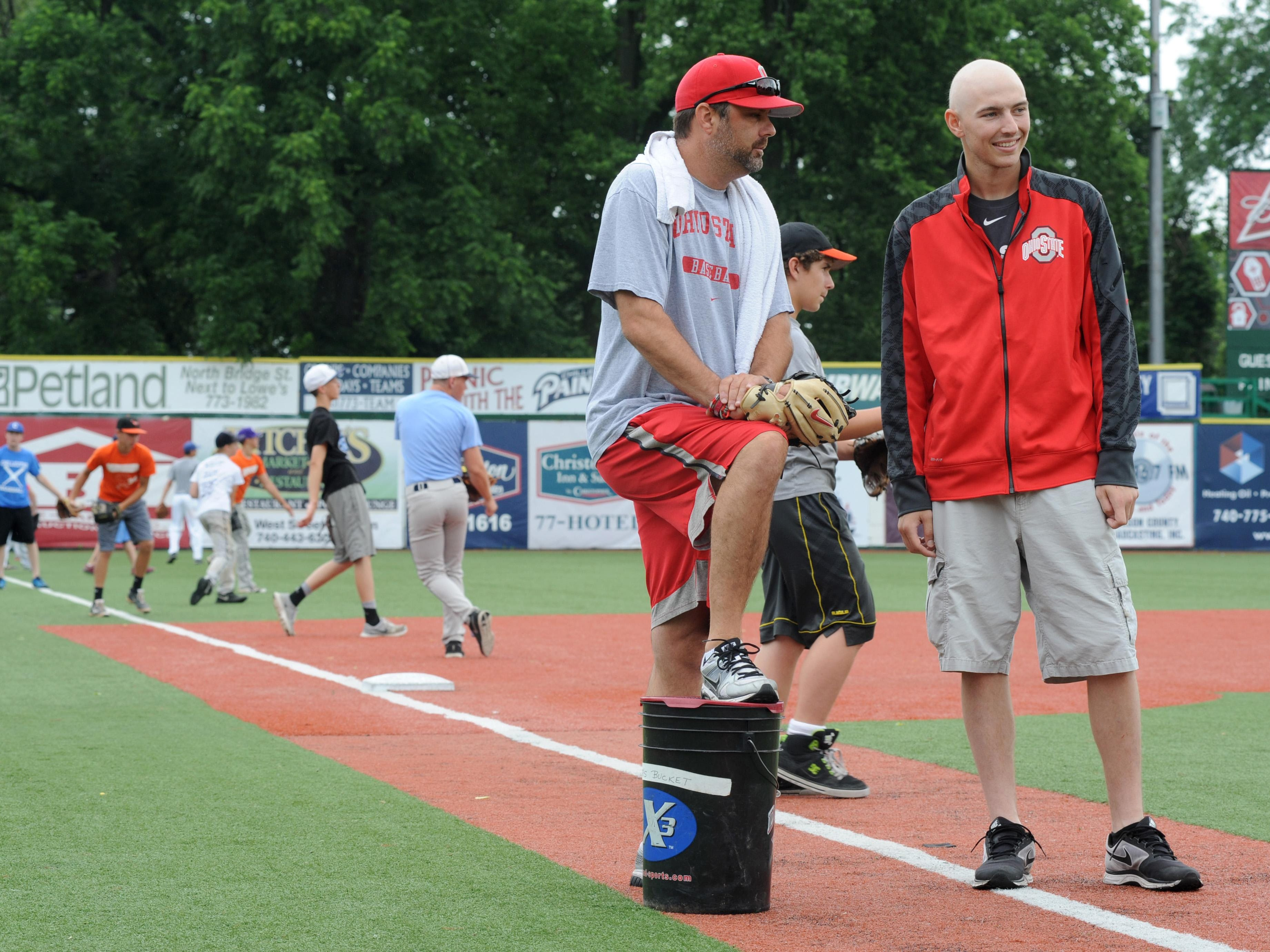 Former Piketon and Ohio State pitcher Zach Farmer, right, talks with Buckeye pitching coach Mike Stafford during the Zach Farmer Strikeout Leukemia pitching camp in June at V.A. Memorial Stadium. Farmer, a former Piketon and Ohio State star pitcher, has died after a 15-month battle with acute myeloid leukemia.