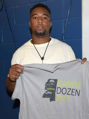 Laurel wide receiver/tight end Octavious Cooley his Dandy Dozen tee shirt from Courtney Cronin, The Clarion-Ledger high school sports editor, after the photo shoot at Mississippi Veterans Memorial Stadium on Tuesday, July 28, 2015.