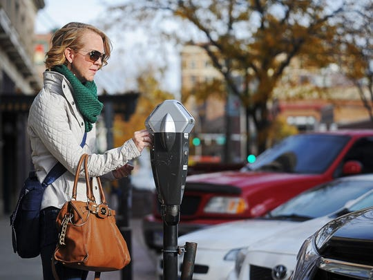 Karla Santi, of Sioux Falls, pays a parking meter along Phillips Avenue.