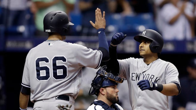 New York Yankees' Donovan Solano, right, high fives Mason Williams after Solano hit a two-run home run off Tampa Bay Rays relief pitcher Erasmo Ramirez during the ninth inning of a baseball game Wednesday, Sept. 21, 2016, in St. Petersburg, Fla. Catching for the Rays is Bobby Wilson.