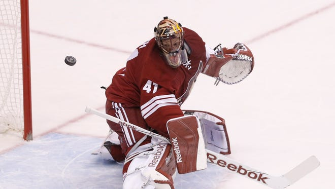 Coyotes goalie Mike Smith makes a save against the Buffalo Sabres during the first period at Gila River Arena in Glendale March 30, 2015.