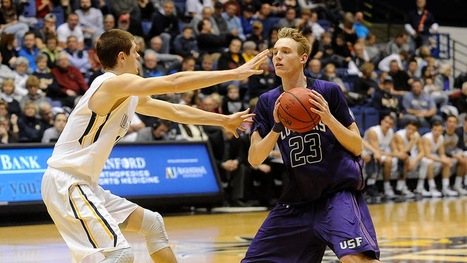 USF's #23 Drew Guebert looks for an open teammate against Augustana's #11 Adam Beyer during basketball action at the Arena in Sioux Falls, S.D., Saturday, Jan. 2, 2016.