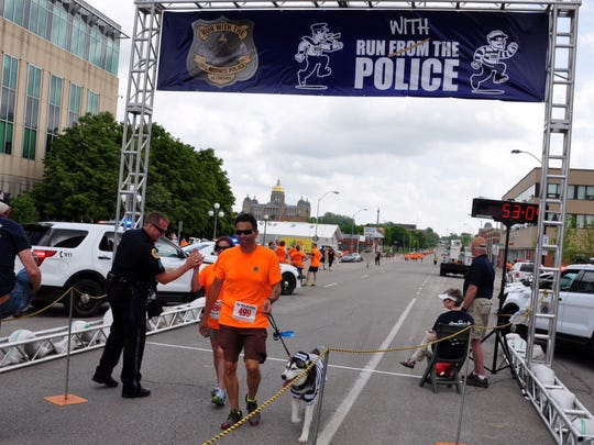 Cricket Piper crosses the finish line at the 2015 Run with the Des Moines Police event.