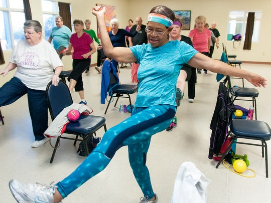 "Cheta Isitua, who says she is ""67 years old going on 25,"" works out with others during a wellness workout at MountainView Senior Circle."