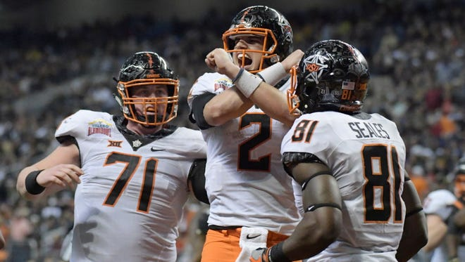 Oklahoma State wide receiver Jhajuan Seales (81), offensive lineman Brad Lundblade (71) and quarterback Mason Rudolph (2) celebrate after scoring a touchdown against Colorado.