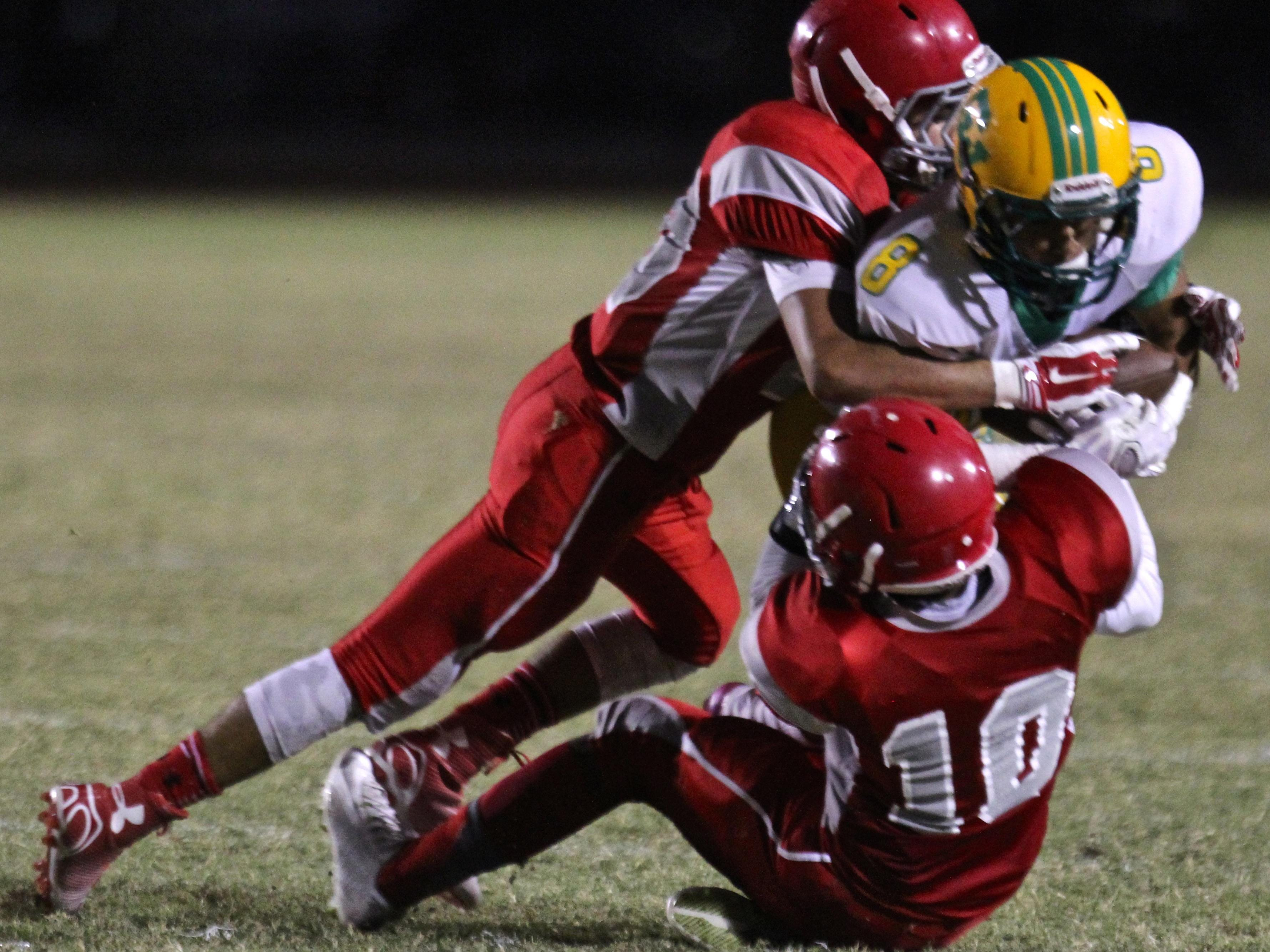 Coachella Valley's Willy Ortiz (8) is tackled by two Rams defenders during the annual Date Bowl matchup in Thermal on Friday.