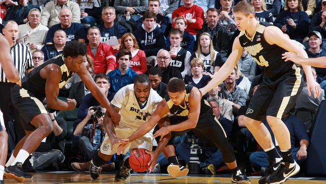 Butler forward Roosevelt Jones (21) scrambles for a loose ball against Purdue forward Caleb Swanigan (50) and guard P.J. Thompson (3) during the Crossroads Classic at Bankers Life Fieldhouse.