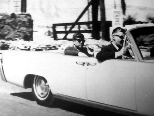 "Pres. John F. Kennedy leaving Bing Crosby's ""Silver Spur Ranch"" in Palm Desert, riding in convertible."