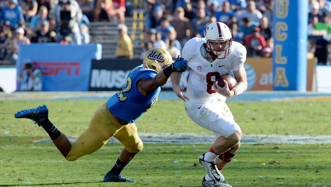Stanford Cardinal quarterback Kevin Hogan (8) runs away from UCLA Bruins linebacker Kenny Young (42) during the second half of the game at Rose Bowl.