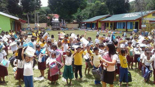 Students hold up their newly acquired supplies at the small school in the Philippines.