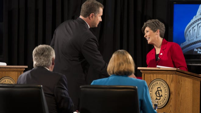 Democratic candidate Bruce Braley and Republican candidate Joni Ernst shake hands at the end of debate.