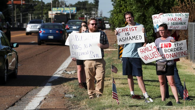 """From left, William Justice, Daniel Wallace, and Lorin Vincent hold signs along Summer Avenue near a federal immigration facility to protest the separation of children from parents. Nearly 2,000 children have been separated from their parents under the Trump administration's """"zero tolerance"""" immigration policy over the past six weeks."""