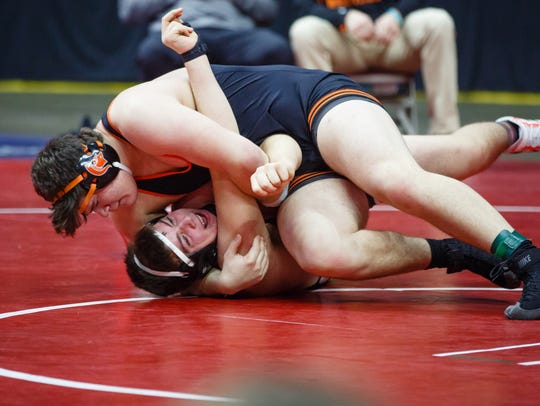 Tyler Linderbaum of Solon, top pins West Delaware,
